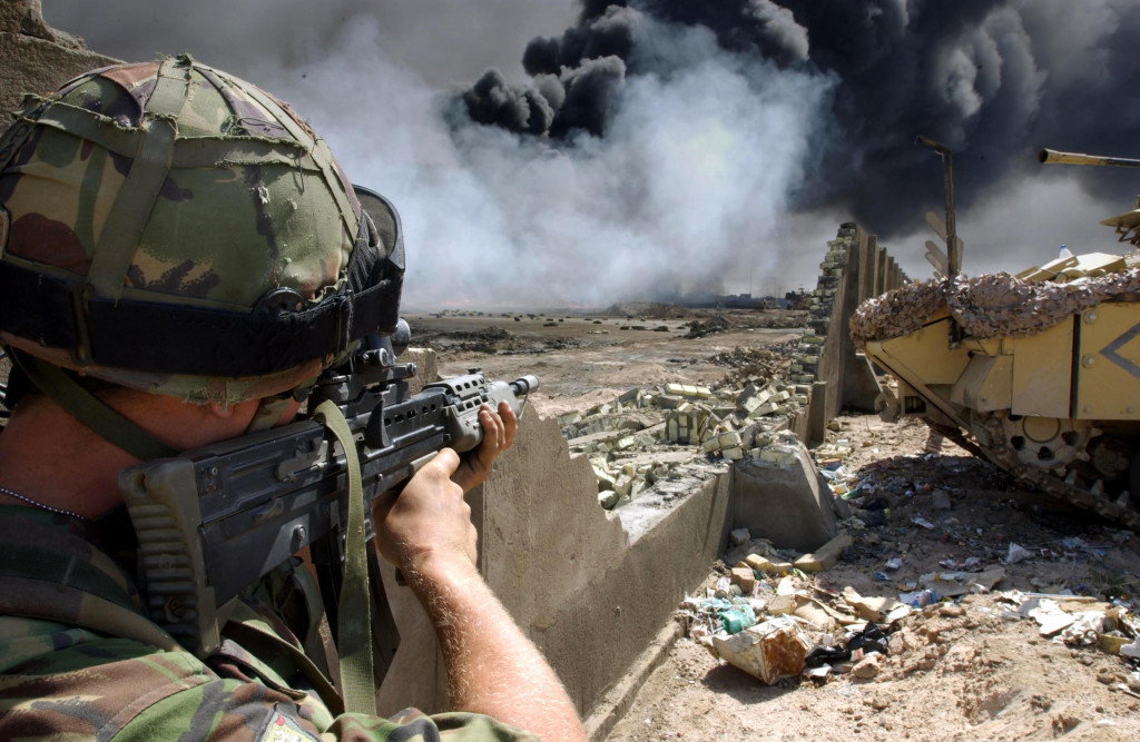 A soldier serving with Number 1 Company 1st Battalion, The Irish Guards, looks for possible Iraqi enemy positions, as Royal Engineer technicians prepare to cap one of the burning oil wells within the city of Basra.